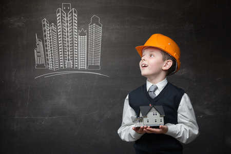 Portrait of boy in hard hat keeping home model and looking at chalky drawing of buildings on grey background photo