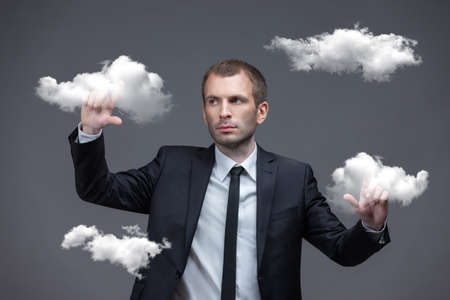Businessman pushes virtual cloud buttons, isolated on grey background. Cloud computing and remote server concept photo
