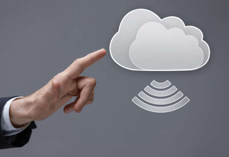 icloud: Close up of finger pushing virtual cloud button, isolated on grey background. Cloud computing and remote server concept