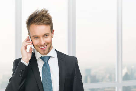 adult intercourse: Half-length portrait of businessman speaking on cell phone against window with urban view. Concept of communication and business Stock Photo