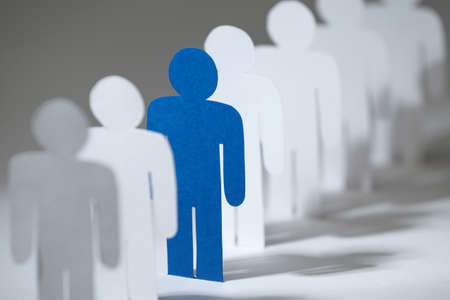 stand out: Close up of group of paper men standing in a row. Lots of similar copies of a paper man, but a blue one stands out among them