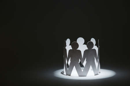 Team of paper doll people holding hands, isolated on black. Concept of friendship and support photo