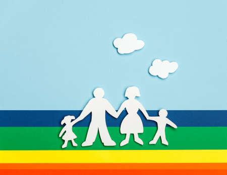 Close up of happy family of paper dolls on colorful background under cutout paper clouds photo