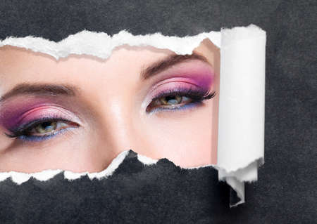 close up image: Close up of female eyes with bright make-up  on torn black paper. Concept of beauty and fashion. Stock Photo