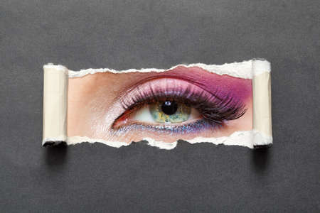 Close up of female eye with pink make-up on torn paper. Concept of fashion and beauty. photo