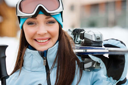 Close up of woman wearing sports jacket and goggles who hands skis photo