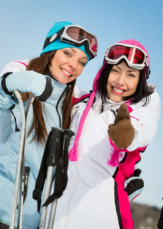 long brown hair: Half-length portrait of two female skier friends thumbing up