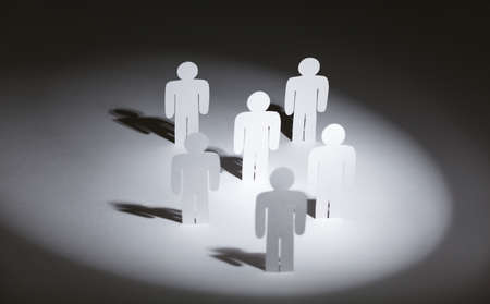 Close up of group of standing papermen in the light photo