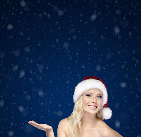 santa cap: Young girl in Christmas cap gestures palm up, on blue snowy background Stock Photo