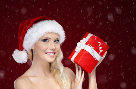 Beautiful woman in Christmas cap hands present, isolated on purple photo