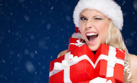 Pretty woman in Christmas cap holds a set of presents, snowflakes background photo