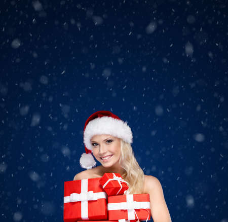Beautiful lady in Christmas cap holds a set of gifts wrapped with red paper,winter background photo