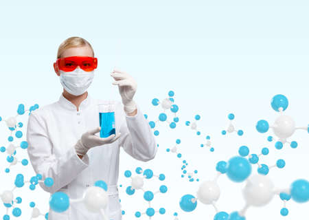 Young doctor in respirator holds a glass beaker on molecular compound background photo