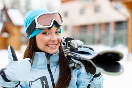 Close up of female wearing sports jacket and goggles who hands skis and thumbs up Stock Photo