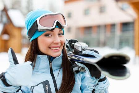 Close-up van vrouwelijke dragen sport jas en bril die ski's en duimen handen omhoog Stockfoto