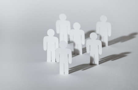 Close up of group of standing papermen. Copies of one paper man. Concept of teamwork, partnership and support photo