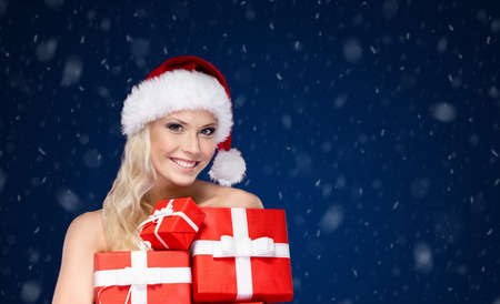 Beautiful lady in Christmas cap holds a set of gifts wrapped with red paper,snowfall background photo