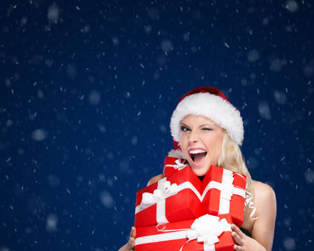 Pretty woman in Christmas cap holds a set of presents, winter background photo