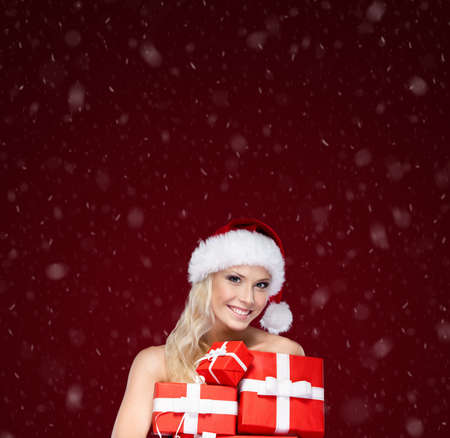 Beautiful girl in Christmas cap holds a set of gifts wrapped with red paper, isolated on purple photo