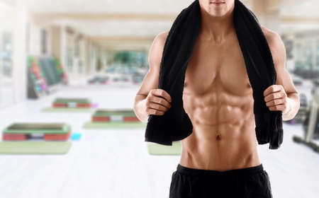 Sexy body of muscular athletic man with towel on the shouldersin gym photo