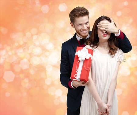 Giving a christmas present man covers eyes of his pretty girlfriend, gold light background photo