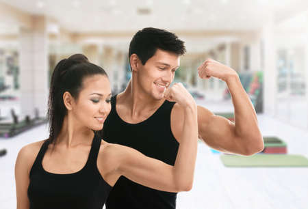 Two sportive trainers showing their biceps in gym Archivio Fotografico