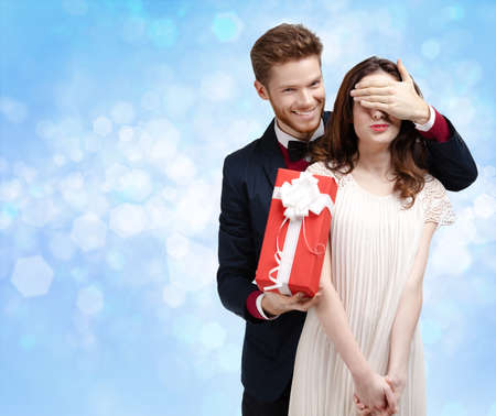 Making a surprise man covers eyes of his pretty girlfriend, blue light background photo
