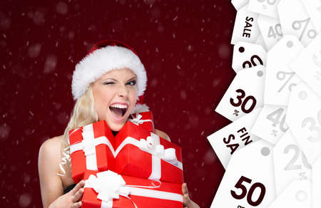 Pretty woman in Christmas cap holds a set of presents from sale, winter sale photo
