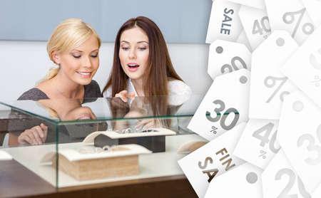 caras emociones: Dos mujeres que buscan en escaparate con joyas en la tienda del joyero, etiquetas de venta fondo. Concepto de la riqueza y la vida de lujo