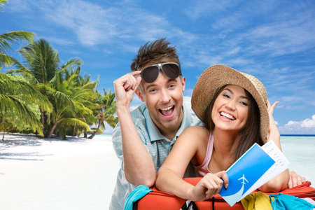 Couple packs up suitcase with clothing for honeymoon trip, tropical beach background. Concept of romantic vacations and lovely honeymoon Фото со стока