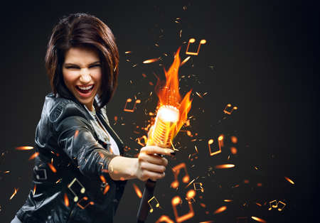 Half-length portrait of female rock musician handing mike on fire, grey background photo
