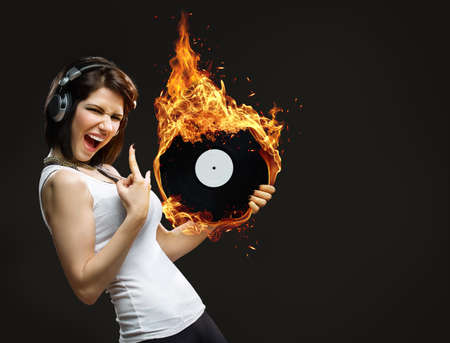 Half-length portrait of teenager with headphones and burning record in hands on black background photo