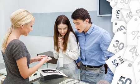 salesperson: Salesperson helps couple to choose wedding rings at jewelers shop. Concept of savings on sale