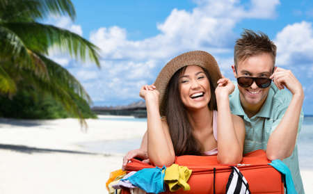 tourist resort: Happy couple packs up suitcase with clothing for trip, tropical island backgrond. Concept of romantic vacations and lovely honeymoon Stock Photo