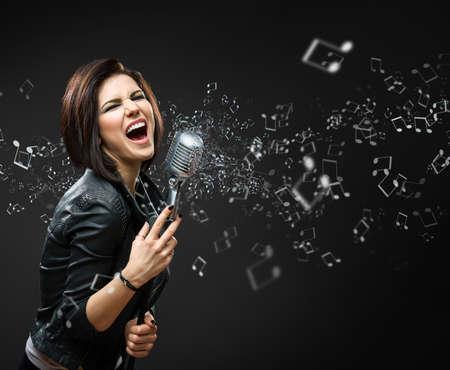 people singing: Half-length portrait of female singing rock musician keeping mike on grey background