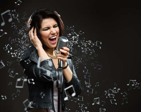 Singing song rock musician with microphone and earphones. Concept of rock music and rave photo