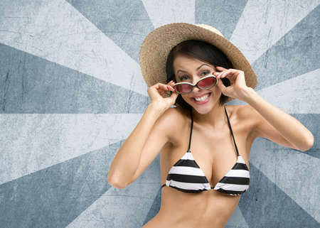 Half-length portrait of female wearing bikini, hat and sunglasses, on striped background. Concept of summer holidays and traveling photo