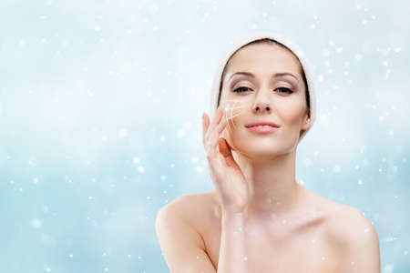 Woman with headband making face moistening procedures in winter time, snowfall background photo