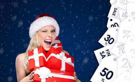 Lucky woman in Christmas cap holds a set of presents, seasonal sale. Blue snowy background photo