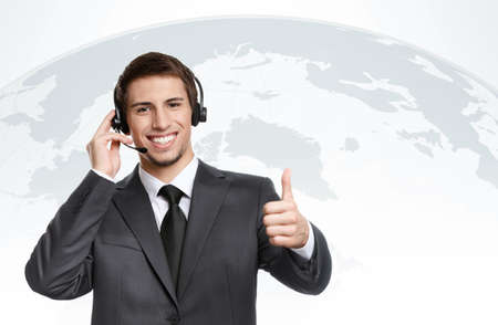 Thumbing up businessman puts earphones with microphone, successful negotiation photo