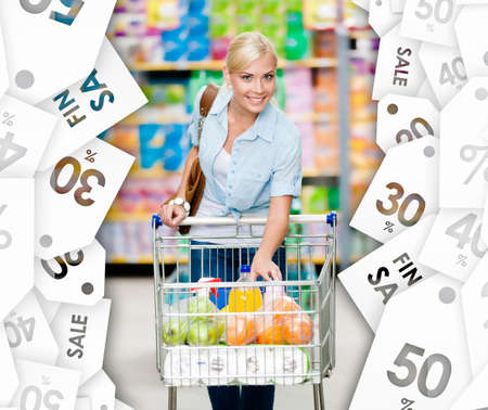 Girl with cart full of food in the shopping center. Sale coupons background. Concept of consumerism, retail and purchase photo