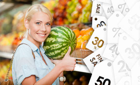 bargain: Girl at the market choosing fruits and vegetables hands watermelon on sale thumbs up Stock Photo