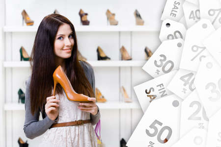 high heeled shoe: Woman keeping brown leather high heeled shoe on sale in shopping center Stock Photo
