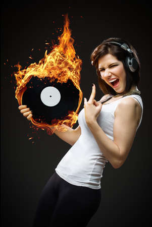 Half-length portrait of teenager with headphones and fiery record in hands on black background photo