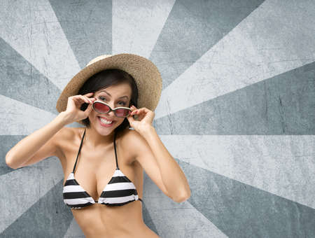 Half-length portrait of female wearing bikini, hat and sunglasses on fantasy background. Concept of summer holidays and traveling photo