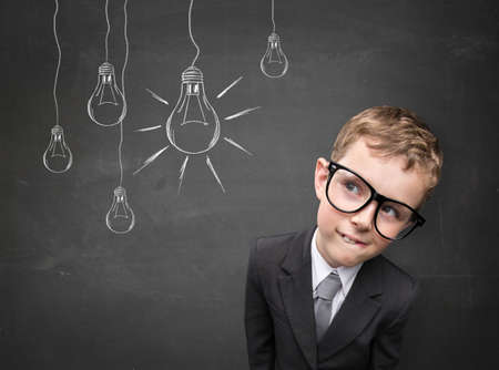 insight: Business kid having an idea. Electric bulbs hanging above his head