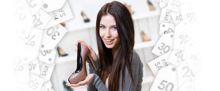 high heeled shoe: Portrait of woman keeping coffee-colored leather shoe in shopping center. Black Friday sale Stock Photo