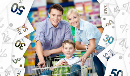Family drives shopping trolley with food. Concept of savings photo