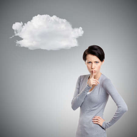 unkind: Pretty woman shows shush gesture, isolated on grey background with cloud