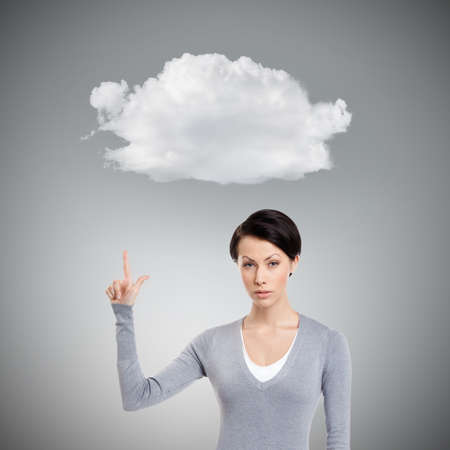 unkind: Young woman shows forefinger, attention sign, isolated on grey background with cloud
